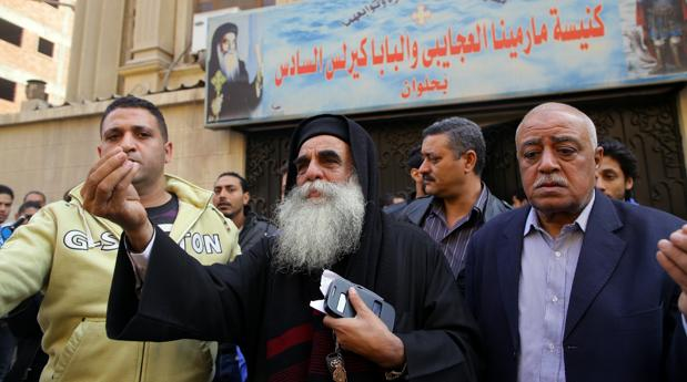 El sacerdote Andoras Azmey habla con la gente tras el atentado de ayer en una iglesia del sur de El Cairo