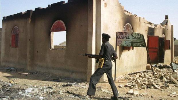 Un policía nigeriano pasa frente a una iglesia quemada por grupos rebeldes musulmanes el pasado mes de febrero
