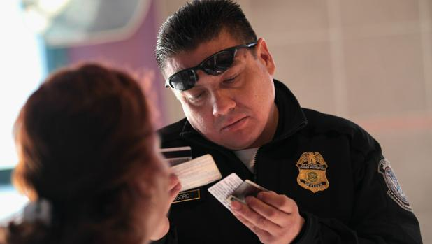 Un agente de Inmigración revisa la documentación de una persona en la frontera entre EE.UU.-México, en 2010