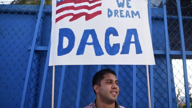 Un ciudadanos sujeta una pancarta a favor del plan migratorio DACA