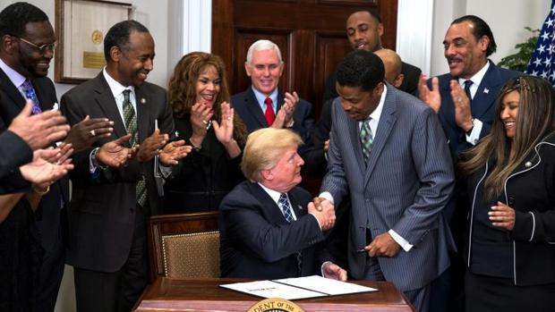 Donald Trump estrecha la mano del presidente del Centro Martin Luther King, Isaac Newton, tras la firma de la proclamación del día del activista de los derechos civiles para los afroamericanos