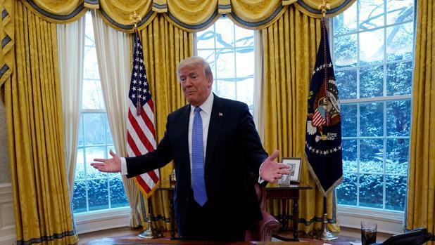Donald Trump aparece en el Despacho Oval junto a su mesa, sobre la que tiene un vaso de su bebida favorita