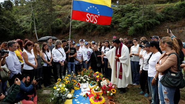 Aura Pérez (de negro, en el centro), tía de Óscar Pérez, asiste a una misa junto a la tumba de su sobrino
