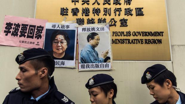 Esta foto de archivo tomada el 3 de enero de 2016 muestra a la policía caminando entre carteles de desaparecidos, entre los que estaba Gui Minhai
