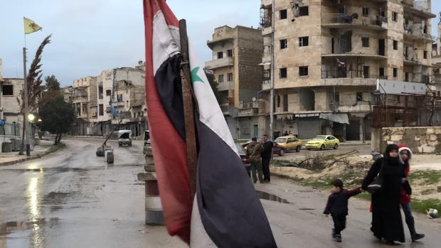 Entrada a Sheikh Mahsoud, el bastión de las YPG en Alepo. En primer término, la bandera del Ejército sirio, a la izquierda, detrás, la de las milicias kurdas