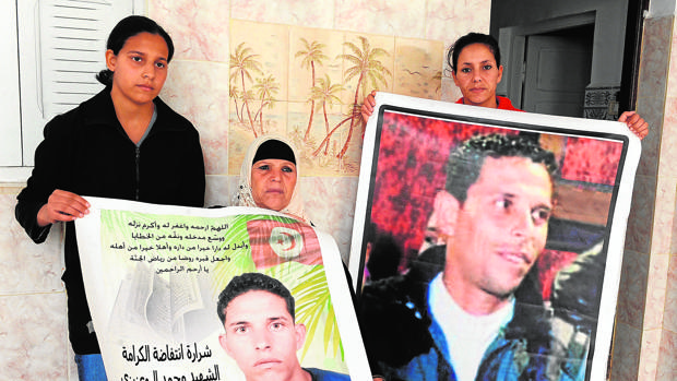 Manoubia Bouazizi (C) y sus hijas muestran carteles del joven Mohamed