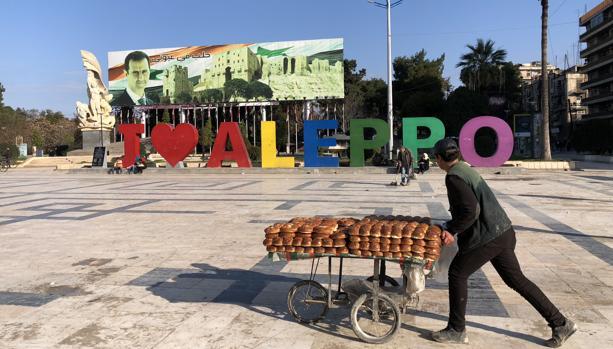 Un vendedor de bollos pasa por delante de un cartel que pone «Yo amo Alepo»