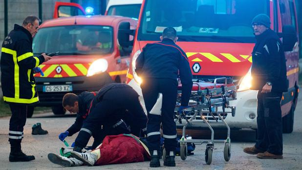 Un hombre recibe asistencia médica tras el enfrentamiento entre inmigrantes cerca del puerto de Calais