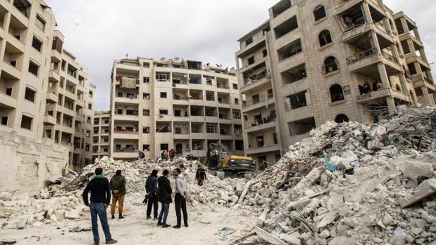 Varias personas observan la búsqueda de supervivientes por parte de voluntarios de Defensa Civil Siria, tras un ataque aéreo ruso sobre Idlib, el pasado 5 de febrero
