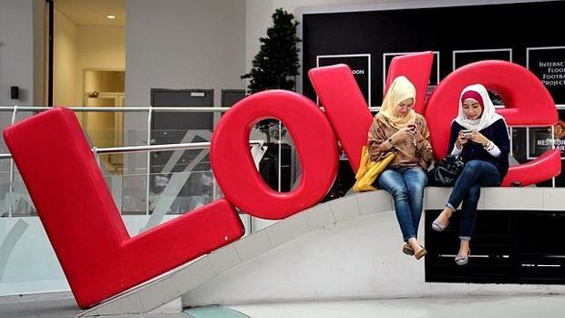Dos jóvenes musulmanas tuitean en la capital de Indonesia en vísperas de San Valentín