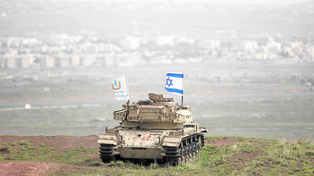 La bandera israelí ondea sobre un viejo carro de combate en el Golán