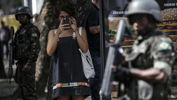 Una mujer toma fotos de los militares este sábado, primer día de la Fuerzas Armadas en Río de Janeiro