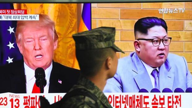 Un soldado surcoreano pasa junto a una pantalla de televisión con las imágenes de los mandatarios de EE.UU. y Corea del Norte
