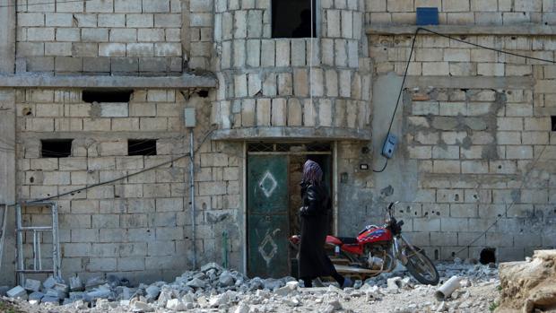 Una mujer inspecciona los destrozos tras una bomba en Idlib (Siria) este lunes