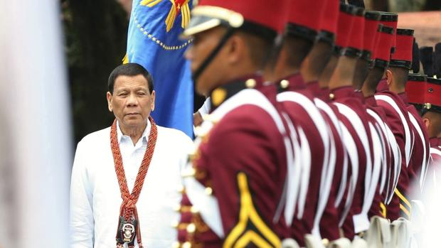 El presidente filipino, Rodrigo Duterte (izq), pasa revista a un grupo de cadetes durante su ceremonia de graduación en la base militar General Mariano Castañeda en la localidad de Silang (Filipinas)