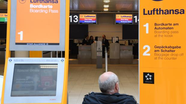 Un viajero se sienta al lado de un mostrador de facturación de Lufthansa