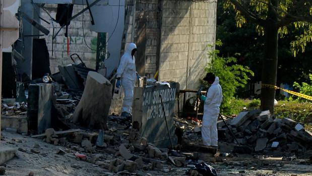 Fotografía de archivo de investigadores de la Policía colombiana revisando el lugar donde explotó un artefacto el pasado 28 de enero, en Barranquilla