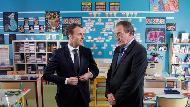 El presidente galo, Emmanuel Macron (izq), conversa con el periodista francés Jean-Pîerre Pernaut (dcha), tras la entrevista mantenida en un aula de un colegio en Berd'huis
