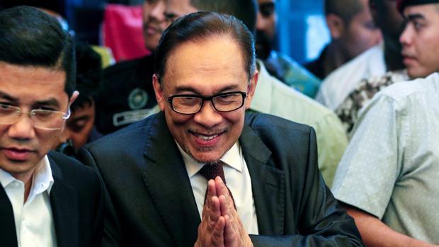 El líder opositor malasio Anwar Ibrahim (c) sonríe a su llegada a una rueda de prensa en Kuala Lumpur (Malasia)
