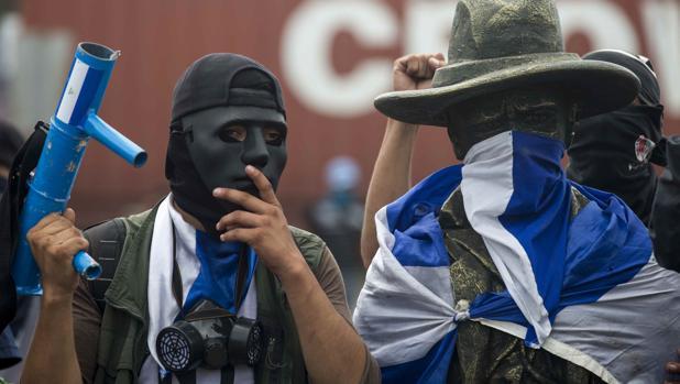 Un joven con una máscara y un lanzamorteros posa junto a una estatua de Augusto César Sandino