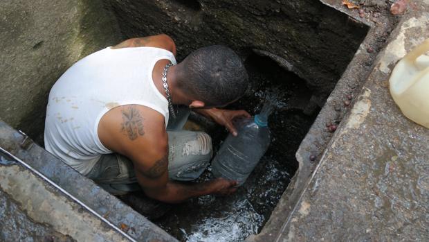 Un hombre se mete dentro de una alcantarilla para recoger agua limpia