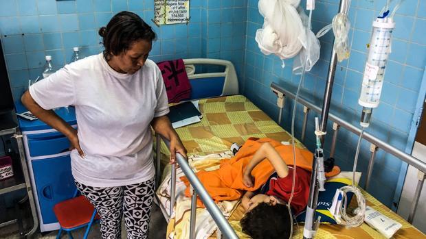 Una mujer, junto a su hijo en una sala de neurocirujía en el hospital infantil «Dr. JM de los Rios», en Caracas