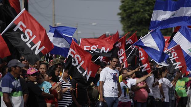 """Un grupo de personas con banderas participa en una actividad conmemorativa al """"repliegue táctico"""" de los sandinistas"""