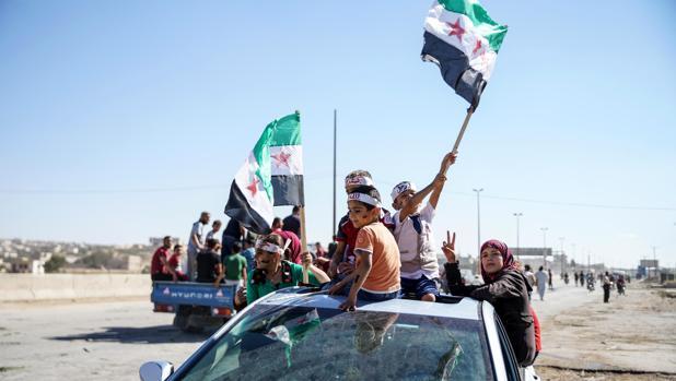 Varias personas ondean banderas sirias revolucionarias durante una protesta en la provincia de Idlib