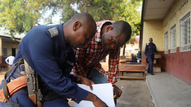 Un policía congoleño y un trabajador de la Comisión Electoral Nacional Independiente del Congo (CENI) preparan una mesa electoral en Kinshasa, República Democrática del Congo