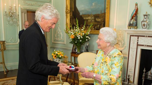 El multimillonario James Dyson, recibiendo la orden del mérito en manos de la Reina Isabel II