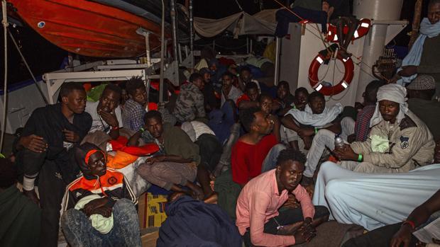 """Varios inmigrantes descansan a bordo del buque """"Lifeline"""" de la ONG alemana Mission Lifeline en el mar Mediterráneo"""