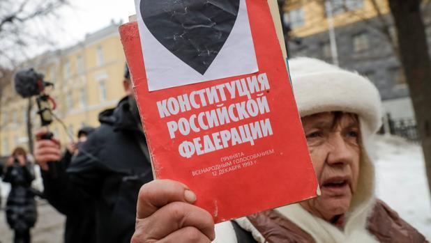Una mujer con un ejemplar de la constitución, en la protesta de Moscú