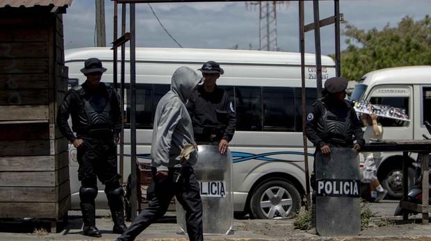 Agentes antidisturbios de la policía nacional resguardan una parda de autobú frente a la Universidad Centroamericana, en Managua