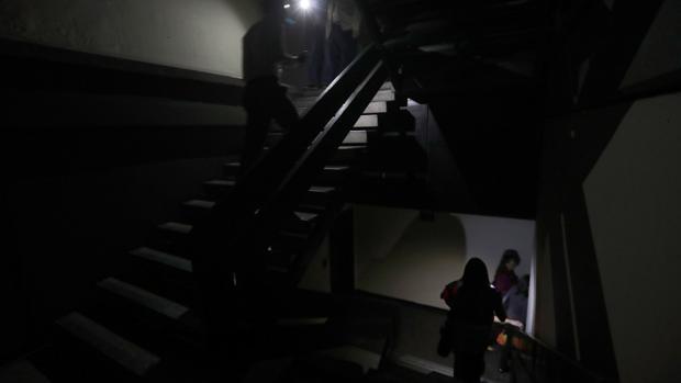 Un grupo de personas baja las escaleras en medio de la oscuridad al interior del edificio de la Asamblea Nacional