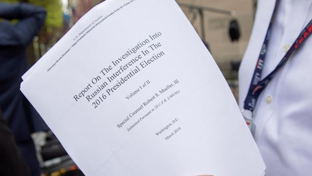 Un periodista sostiene una copia impresa de la versión redactada de la declaración del fiscal especial Robert Mueller