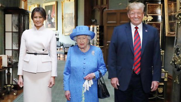 La reina Isabel II, entre Melania y Donald Trump, durante la visita al castillo Windsor en 2018