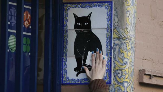 Una mujer pasa su décimo por el lomo del gato negro de la administración del mismo nombre en Sevilla