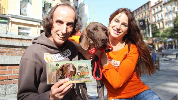 Nacho Paunero enseña el número de la lotería solidaria de El Refugio elegido por Macario