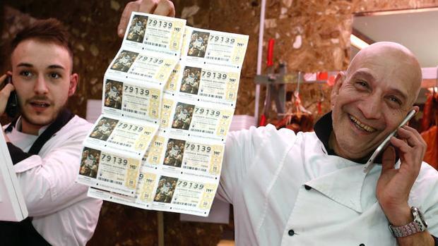 Dos carniceros premiados posan con sus boletos