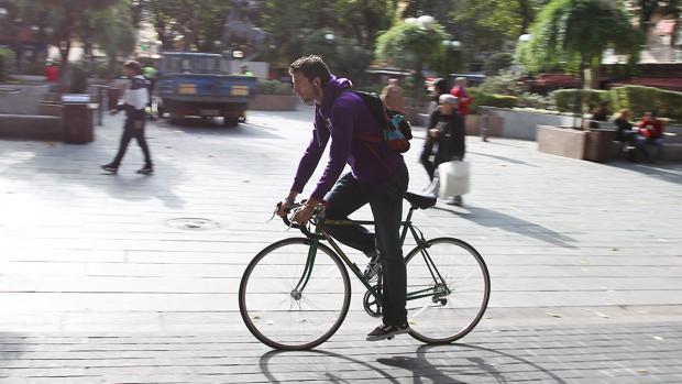Un hombre se desplaza por la ciudad con su bicicleta