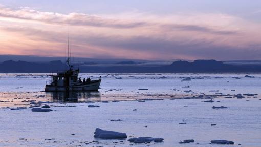 Barco navegando entre pequeños icebergs en el fiordo de Jakobshavn (Groelandia)