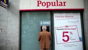 Un hombre utiliza el cajero automática en una oficina del Banco Popular
