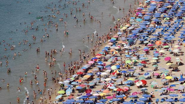 Imagen de archivo de la playa de Levante abarrotada de turistas en Benidorm