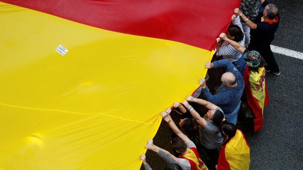 Varios manifestantes sujetan una bandera española de gran tamaño