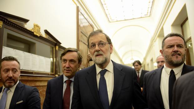 El presidente del Gobierno, Mariano Rajoy (centro), en el pasillo del Congreso