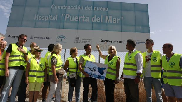 La comitiva del PP, bajo el cartel de un proyecto abandonado