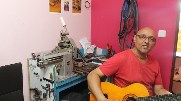 Ignacio Zambrana con su guitarra en su taller de zapatería