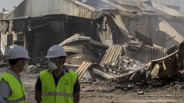 Dos operarios junto a la factoría incendiada