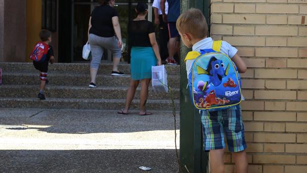 Un niño en la puerta de un colegio en el inicio del curso escolar