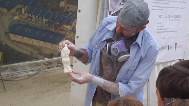 Un escultor muestra una de sus piezas a unos niños